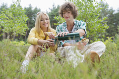 Young male hiker pouring coffee for woman while relaxing in field Stock Photography