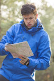 Young male hiker reading map in forest Stock Photography