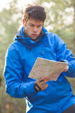 Young male hiker reading map in forest Royalty Free Stock Photos