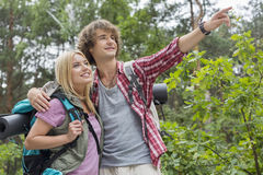Young male hiker showing something to woman in forest. Young male hiker showing something to women in forest Royalty Free Stock Photography