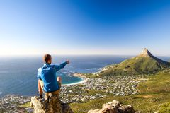 Young male hiker sitting on a rock at Kasteelspoort Hiking Trail in Table Mountain National Park in Cape Town Royalty Free Stock Photos
