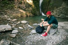 Young tourist camping with backpack near a waterfall in forest. stock image