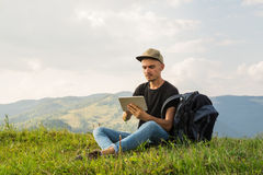 Young male hiker uses tablet pc on vacation Royalty Free Stock Image