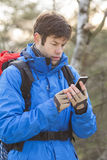 Young male hiker using smart phone in forest Stock Photos