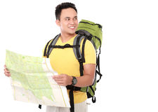 Young male hiking with backpack and map. Portrait of young male hiking with backpack holding map and looking away Royalty Free Stock Image