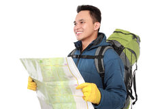 Young male hiking with backpack and map. Portrait of young male hiking with backpack holding map and looking away Royalty Free Stock Photography