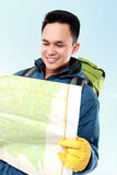 Young male hiking with backpack and map. Portrait of young male hiking with backpack looking at the map isolated on white background Royalty Free Stock Images