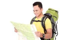 Young male hiking with backpack and map. Portrait of young male hiking with backpack looking at the map isolated on white background Stock Photo