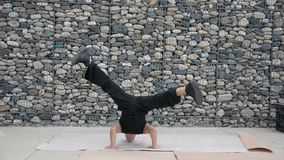 Young male hip-hop dancer dancing outside. Young male trendy hip-hop dancer outside, doing break-dance in city setting in front of stone wall stock video