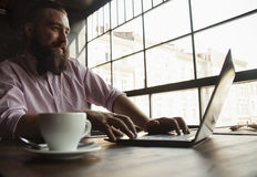 Young male hipster freelancer working with laptop Stock Images