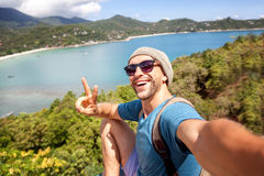 Young male hipster traveler doing selfie overlooking the tropica. L sea. Adventure, vacation, wonderlust, internet, technology concept Stock Images
