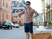 Young male hitchhiker. Standing with his suitcase in an urban street thumbing a lift Royalty Free Stock Image