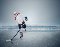 Young male hockey player on the ice Stock Photos