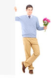 Young male holding flowers next to a panel Royalty Free Stock Photography