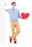 Young male holding a panel and red heart Royalty Free Stock Photography