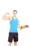 Young male holding plate full of vegetables and showing his musc Stock Photography
