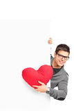Young male holding a red heart shaped pillow Royalty Free Stock Images