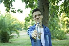 Young male is holding water bottle in park royalty free stock image
