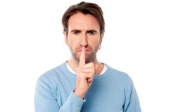 Young male holds finger on his lips Royalty Free Stock Image