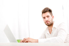 Young male at home with a laptop Stock Images