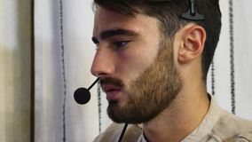 Young male home worker with headset. Young male home worker talking with customer or client through headset and microphone, working from his living room in front Stock Photo