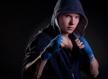 Young male in hood. Young man in a hood on black background Royalty Free Stock Photos