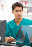 Young male hospital doctor at desk. Examining x-ray Royalty Free Stock Images