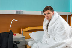 Young male ill patient sitting on the hospital bed covered with Royalty Free Stock Photo