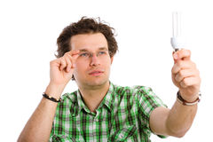 Young male inspecting energy saving bulb, isolated Stock Photo