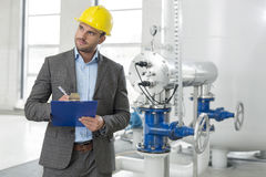 Young male inspector writing on clipboard while looking away in industry Royalty Free Stock Images