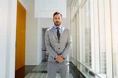 Young male intelligent CEO in formal wear is standing in modern office interior royalty free stock image