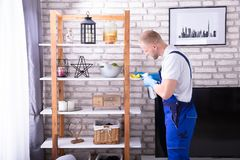 Young Male Janitor Cleaning Shelf. Side View Of A Young Male Janitor Cleaning Shelf In House stock photos