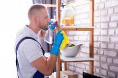 Young Male Janitor Cleaning Shelf. Side View Of A Young Male Janitor Cleaning Shelf In House royalty free stock photography