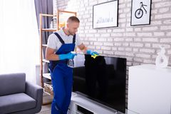 Male Janitor Cleaning Television. Young Male Janitor Cleaning Television With Soft Cloth stock photography