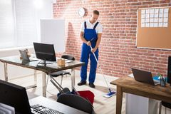 Male Janitor Mopping Floor. Young Male Janitor Mopping Hardwood Floor At Workplace Stock Images
