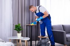 Janitor Wiping Wooden Furniture. Young Male Janitor Wiping Wooden Furniture In House royalty free stock photo