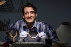 The young male jeweller working at night in his workshop. Young male jeweller working at night in his workshop Royalty Free Stock Images