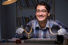 The young male jeweller working at night in his workshop. Young male jeweller working at night in his workshop Stock Photography