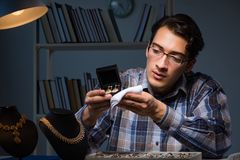 The young male jeweller working at night in his workshop. Young male jeweller working at night in his workshop Royalty Free Stock Photo