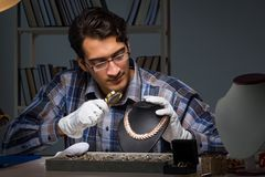 The young male jeweller working at night in his workshop. Young male jeweller working at night in his workshop Royalty Free Stock Photos