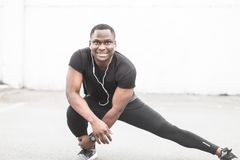 Young male jogger athlete training and doing workout outdoors in city. a black man resting after a workout and listening. To music and watching a sports watch royalty free stock images
