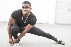 Young male jogger athlete training and doing workout outdoors in city. a black man resting after a workout and listening. To music and watching a sports watch royalty free stock image