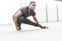 Young male jogger athlete training and doing workout outdoors in city. a black man resting after a workout and listening. To music and watching a sports watch stock images