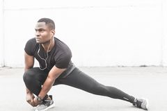 Young male jogger athlete training and doing workout outdoors in city. a black man resting after a workout and listening. To music and watching a sports watch stock photos