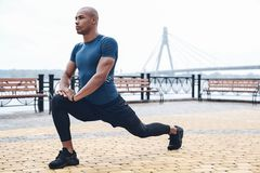 Young male jogger athlete training and doing workout outdoors in. City stock photos