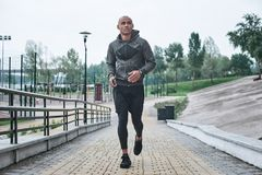 Young male jogger athlete training and doing workout outdoors in. City stock photography