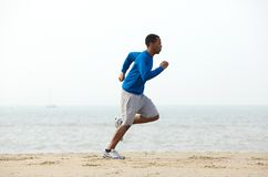 Young male jogger exercising at the beach Royalty Free Stock Photography