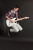 Young male jumping with guitar Royalty Free Stock Photos
