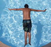Young male jumping to pool Royalty Free Stock Image