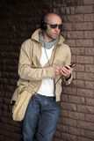 Young male in khaki listen to music, outdoor Royalty Free Stock Photography